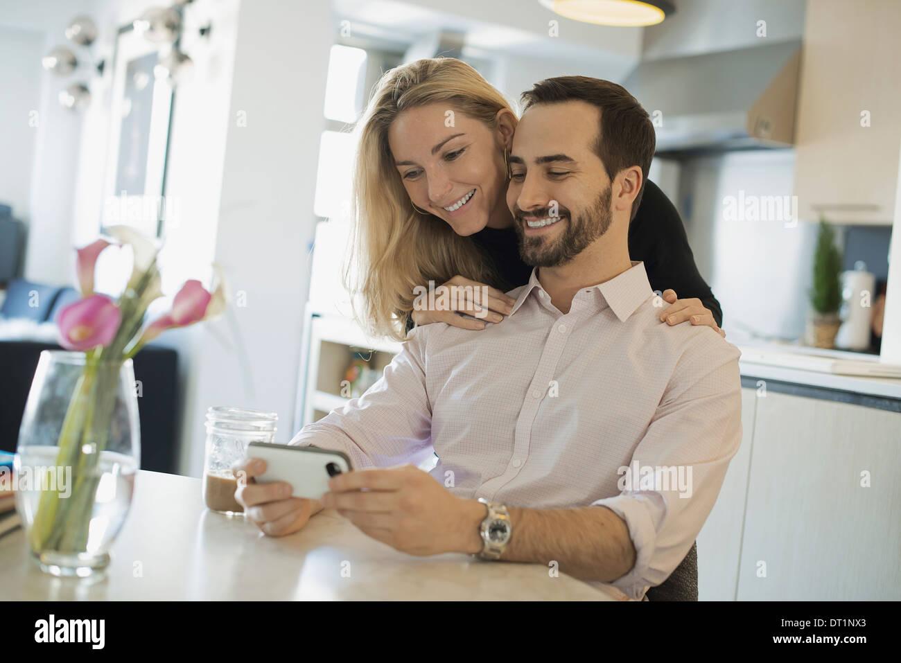 Pareja en el hogar mirando fotos en el smartphone Imagen De Stock