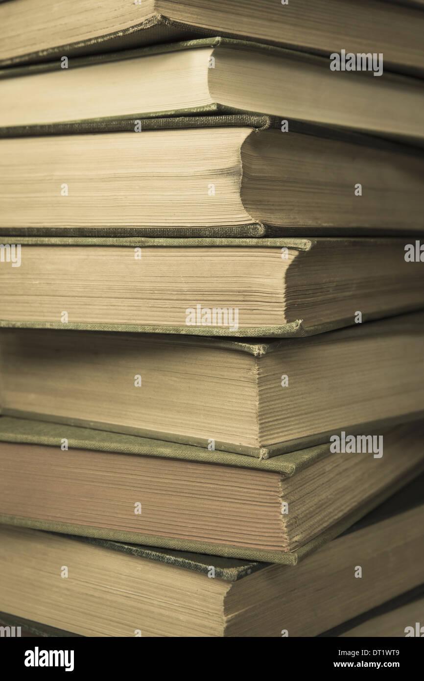 Una pila de viejos libros de tapa dura con bordes desgastados y envejecidos amarillea el papel Imagen De Stock