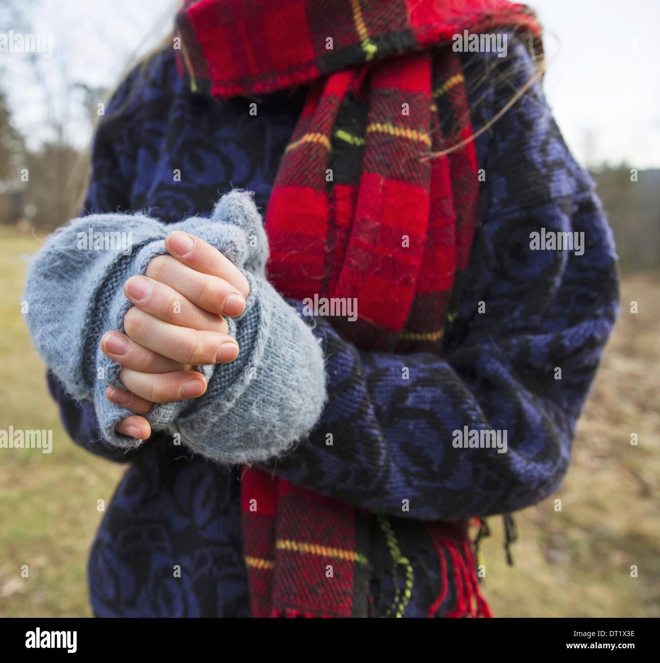 Una mujer en un tartan bufandas y manoplas de lana tejida manteniendo sus manos cálidas en clima frío Imagen De Stock