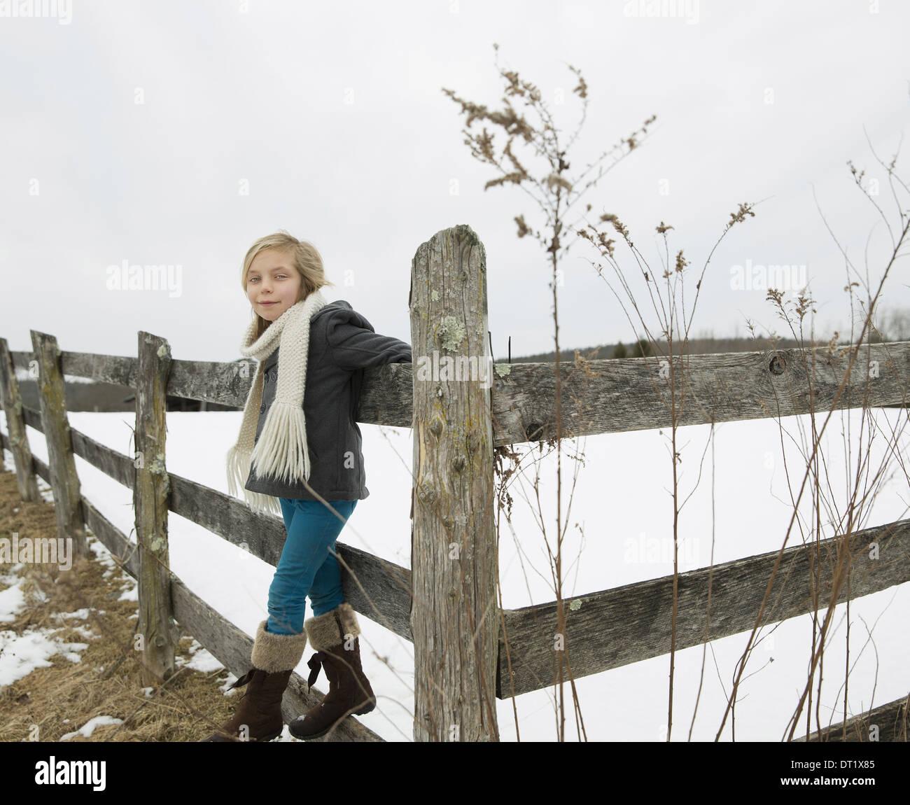 Una granja en la nieve, una niña con un sombrero y una bufanda y botas, apoyándose en una valla Foto de stock