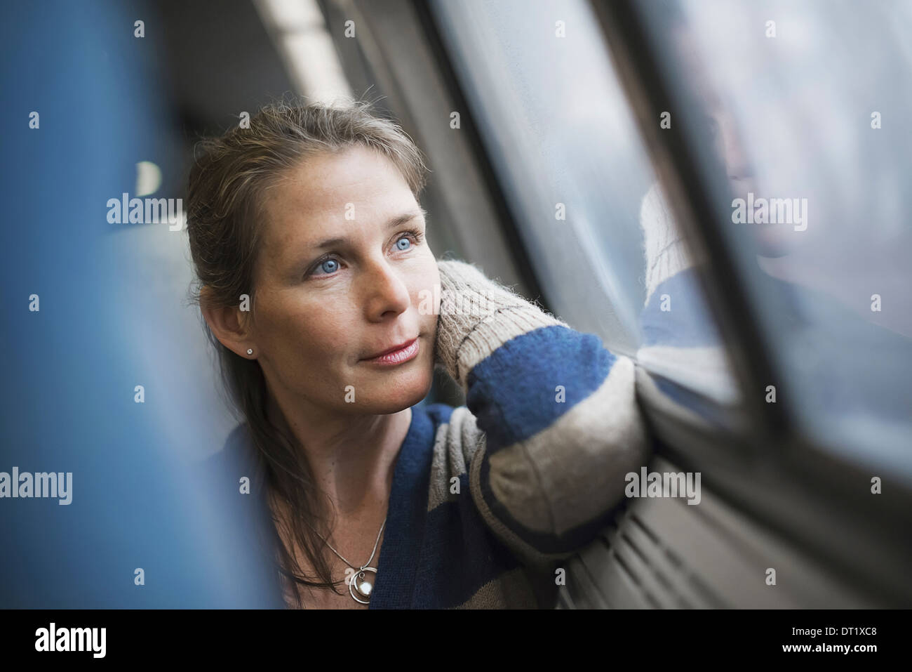 Una mujer sentada en un asiento de ventanilla en un carro de tren descansando su cabeza sobre su mano, mirando a la distancia Imagen De Stock