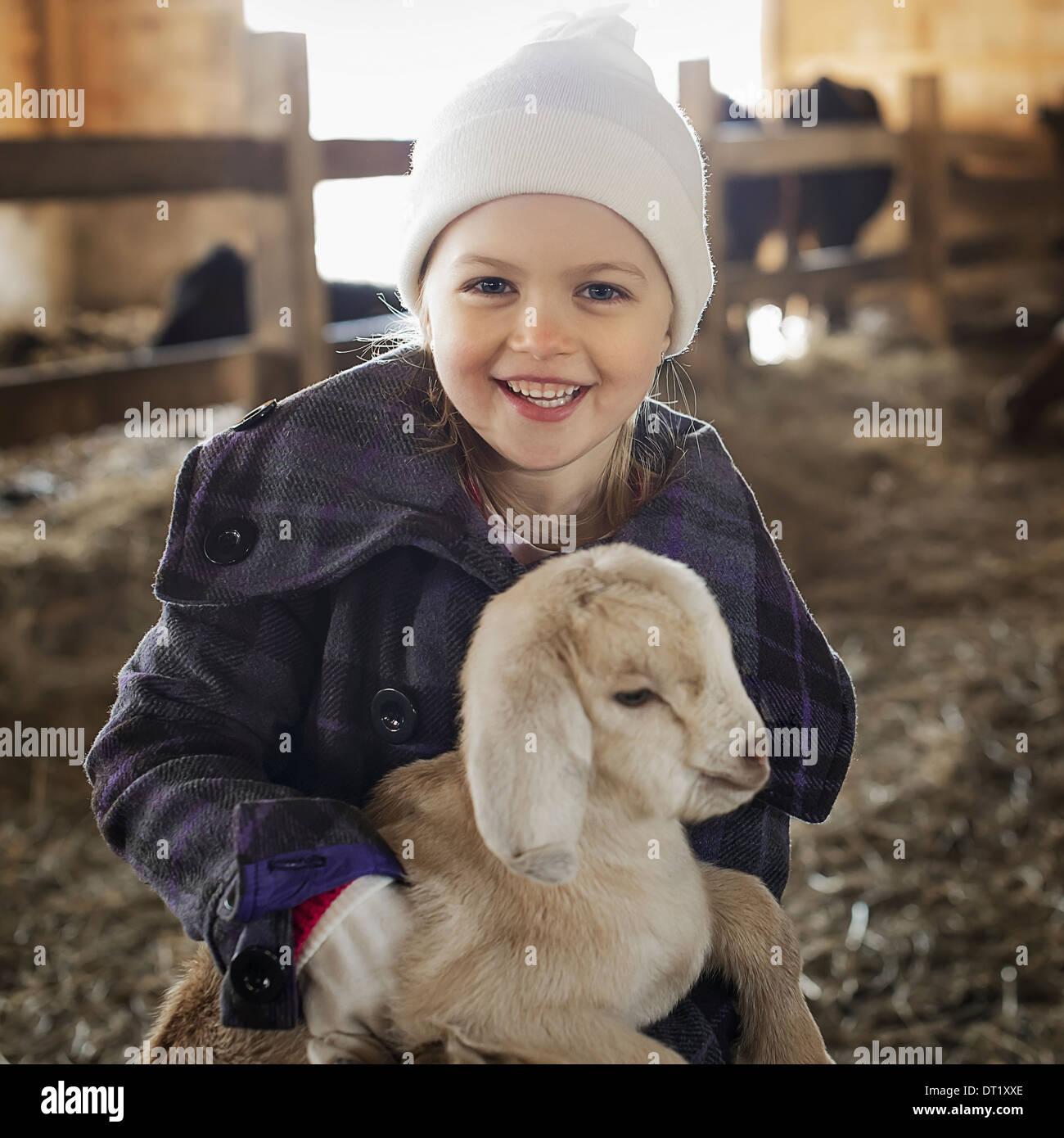 Un niño en el animal derramada holding y acariciar a un bebé de cabra Imagen De Stock