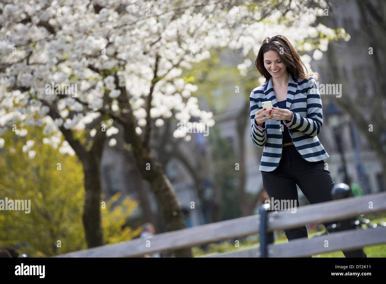 Afuera de la ciudad en la época de primavera en el parque de la ciudad de Nueva York en los árboles en flor blanca una mujer de pie controlar su teléfono móvil Imagen De Stock