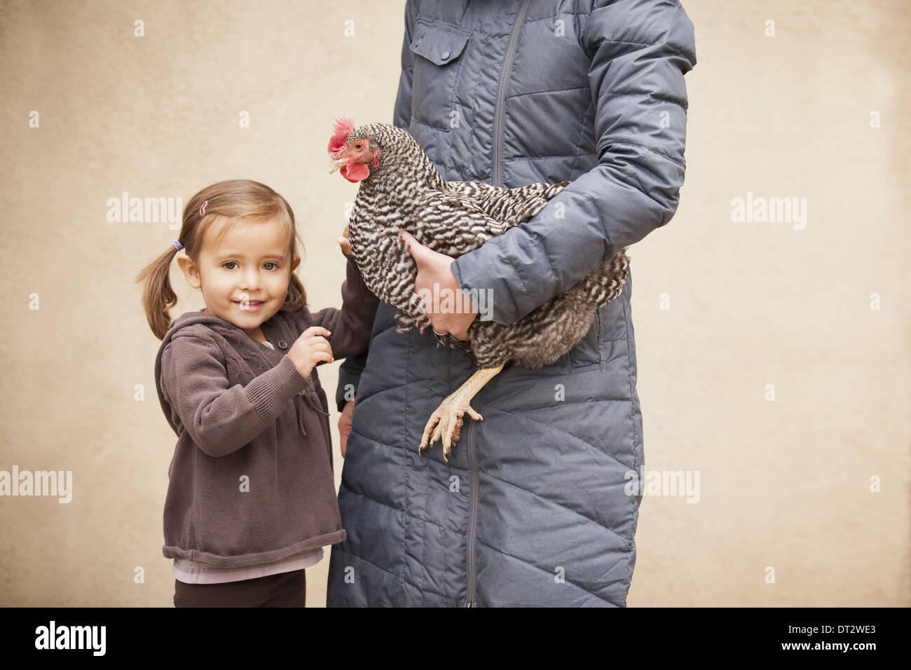 Mujer sosteniendo un pollo blanco y negro con un rojo coxcomb bajo un brazo a una joven muchacha a su lado sosteniendo su otra mano Imagen De Stock