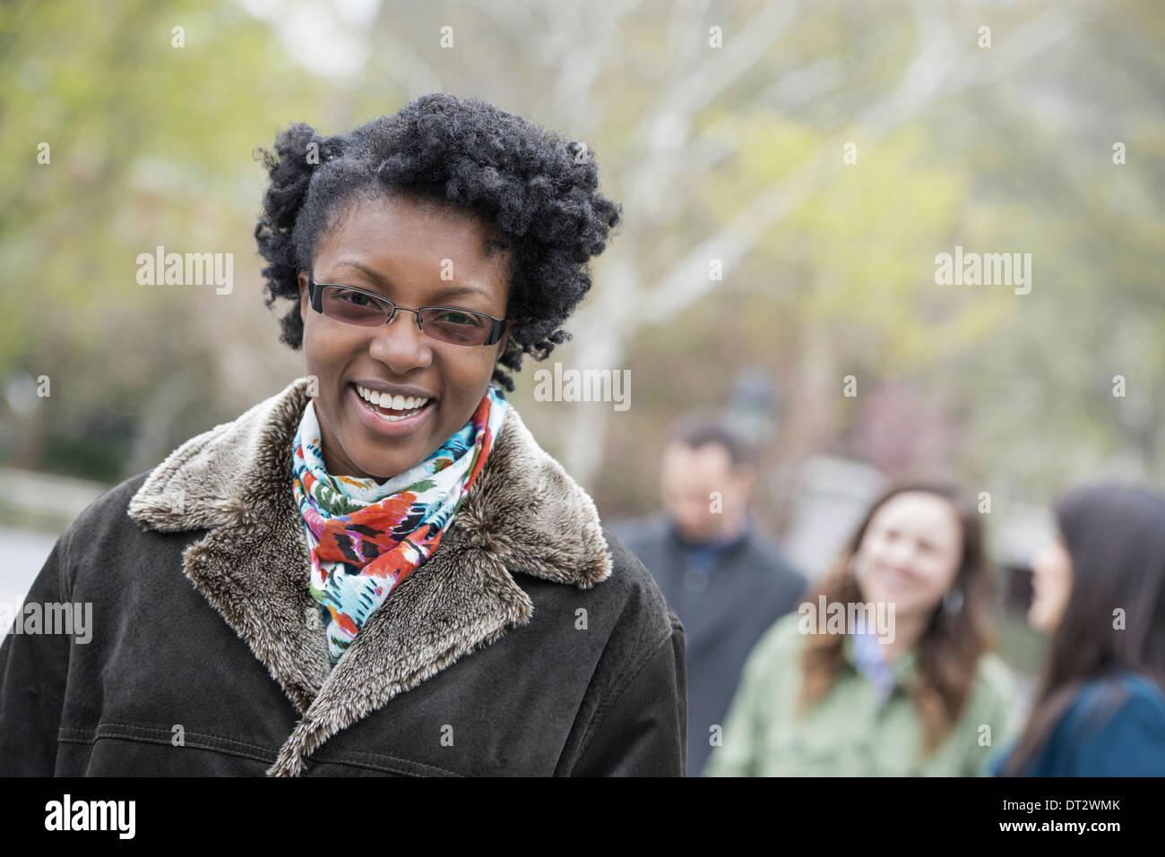 Un grupo de personas en un parque de la ciudad a una joven en un escudo con un collar grande sonriendo y mirando la cámara Imagen De Stock