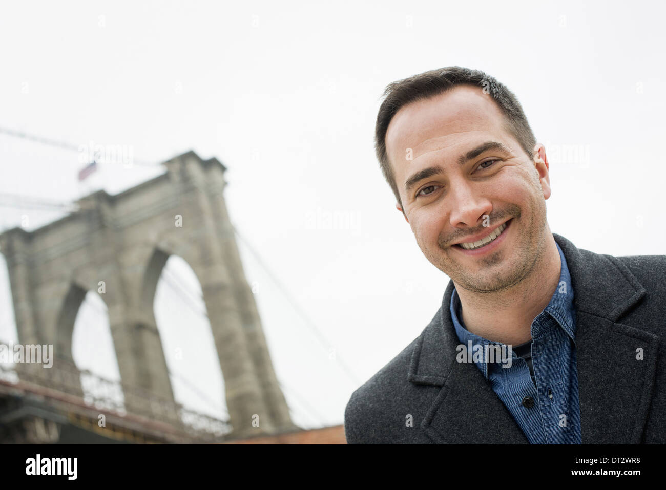 La ciudad de Nueva York el Puente de Brooklyn cruzando el East River, un hombre que mira a la cámara y sonriendo Imagen De Stock
