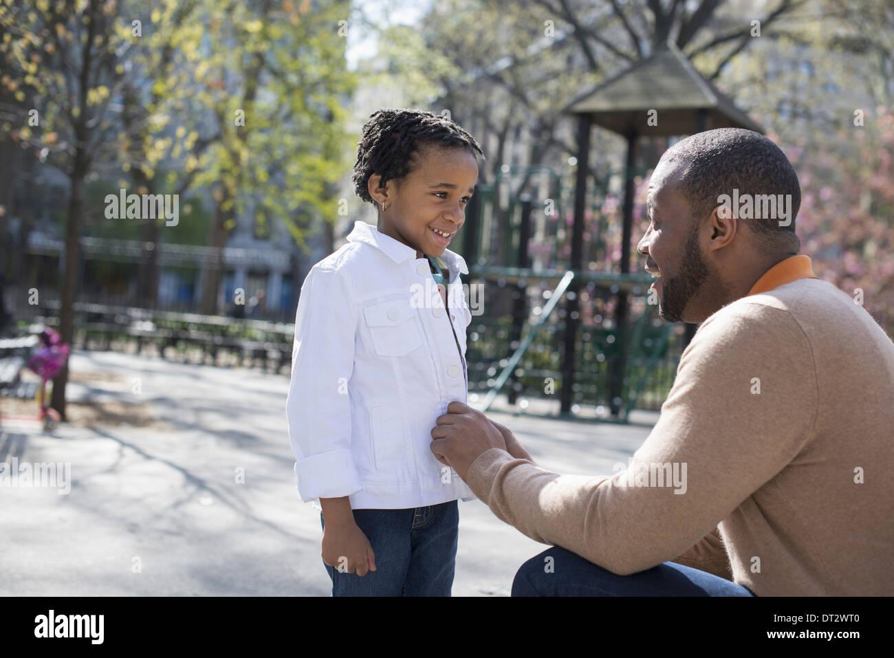 Un padre arrodillado y abotonarse la chaqueta de su hijo. Imagen De Stock
