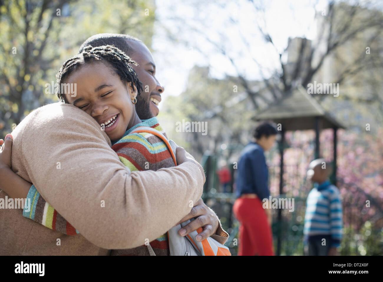 Una familia junto a un padre abrazando a su hijo Imagen De Stock