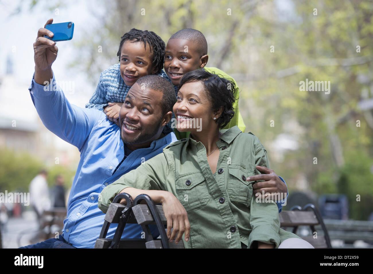 A padres y madres de familia y dos niños tomando una fotografía con un teléfono inteligente. Imagen De Stock