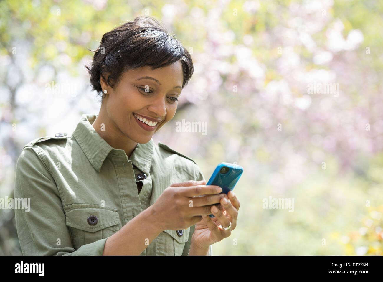 Sol y flor de cerezo a la mujer controlar su teléfono inteligente. Imagen De Stock