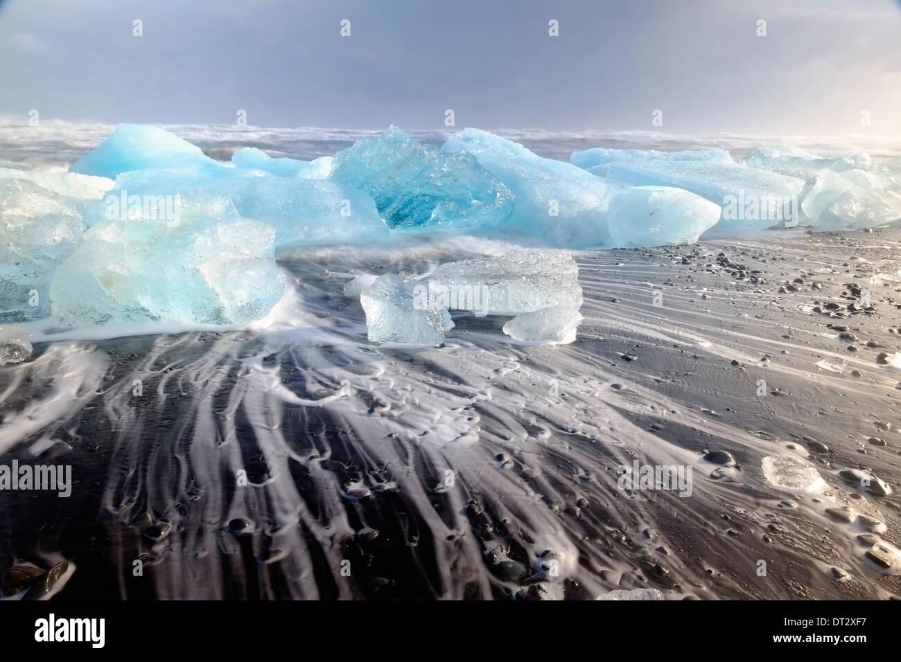 Los IceBergs y las olas en la playa de Jokulsarlon, Región Polar, en el sur de Islandia Imagen De Stock