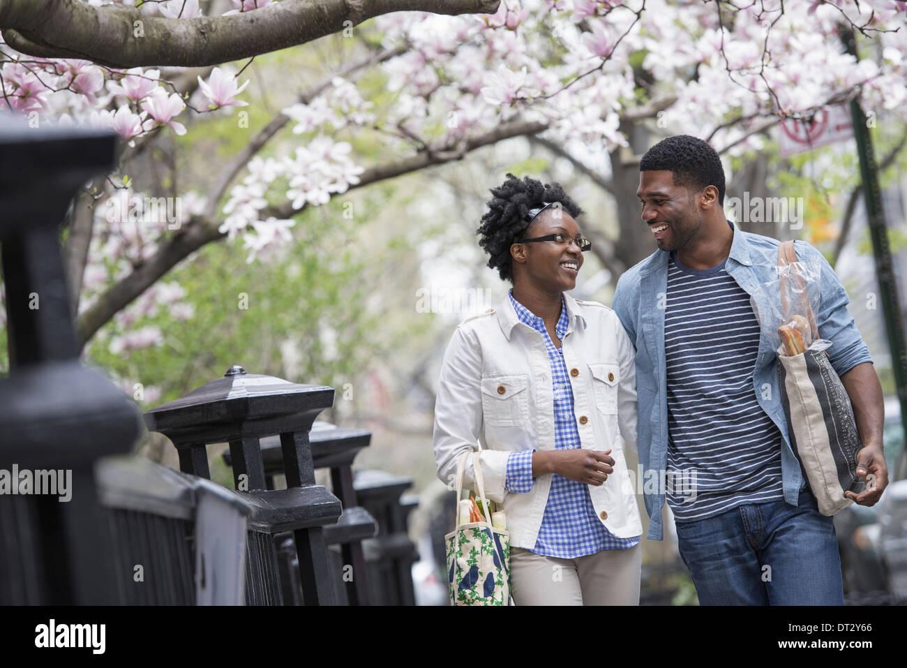 Una pareja a caminar en el parque al lado de llevar bolsas de la compra. Imagen De Stock