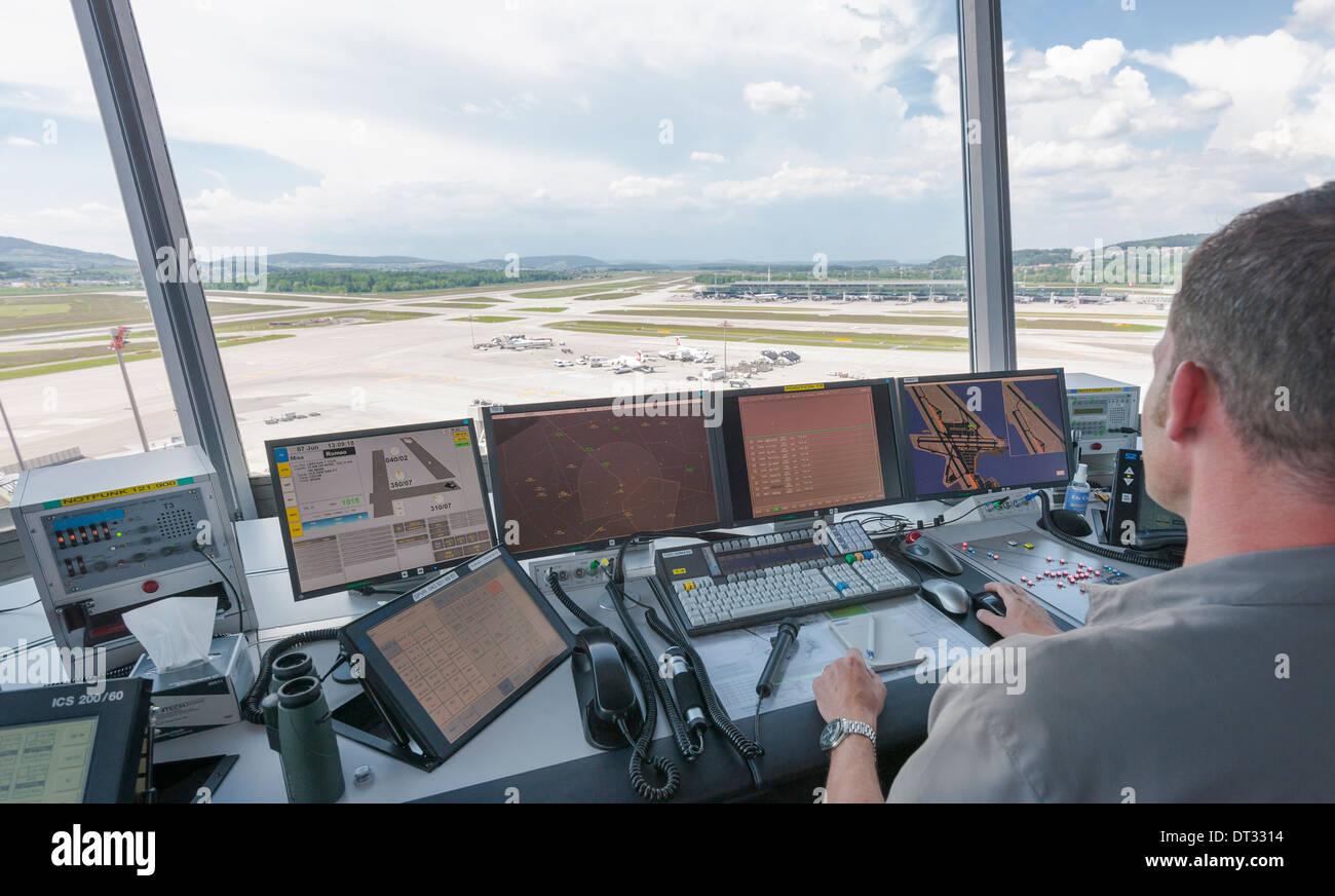 Un controlador de tráfico aéreo en la torre de control del aeropuerto internacional de Zúrich Kloten/está supervisando el aeródromo del aeropuerto. Foto de stock