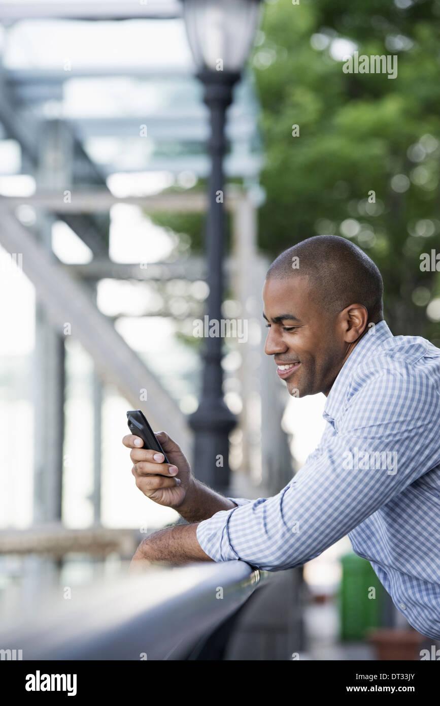 Un hombre en shirtsleeves controlar su teléfono inteligente. Imagen De Stock