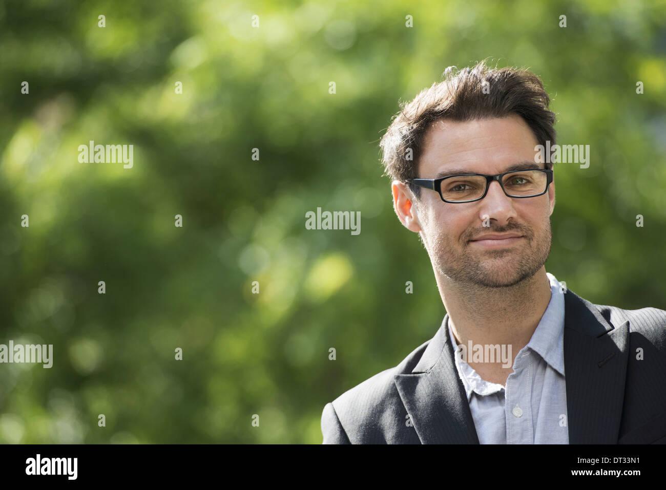 Un hombre con cabello oscuro corto y gafas sonriendo ante la cámara Foto de stock
