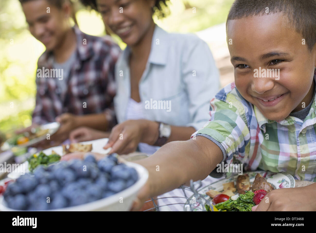 Una familia de picnic a la sombra de un bosque de adultos y niños sentados en una mesa Imagen De Stock
