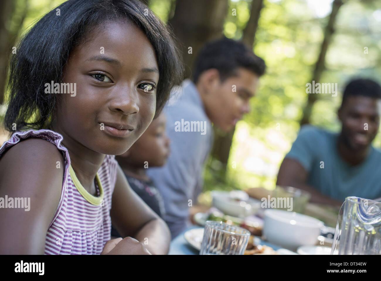 Una chica joven y adultos sentados en la mesa Imagen De Stock