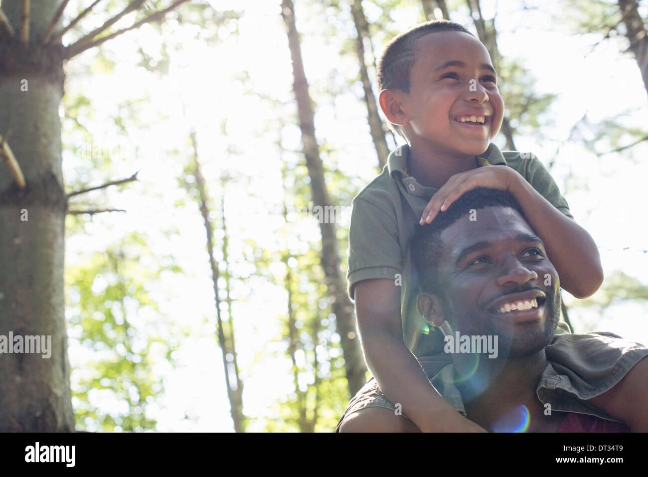 Un muchacho sentado sobre los hombros de su padre Imagen De Stock