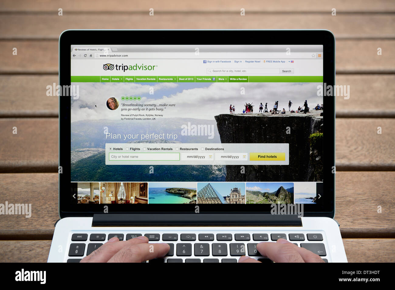 El sitio web de Tripadvisor en MacBook contra un banco de madera de fondo al aire libre incluyendo un hombre de dedos (uso Editorial solamente). Imagen De Stock