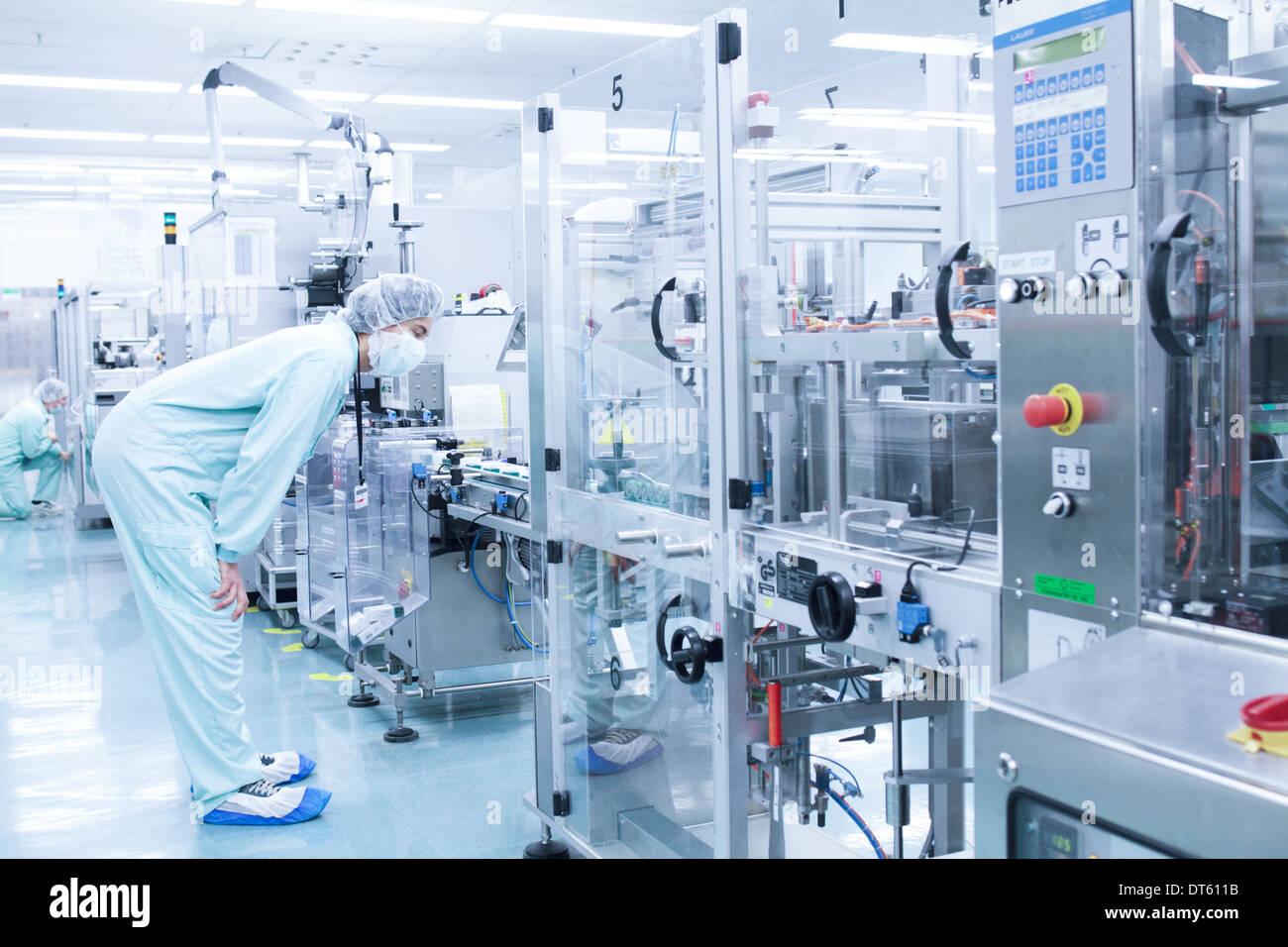 Técnico de laboratorio doblando a examinar detenidamente en la máquina Imagen De Stock