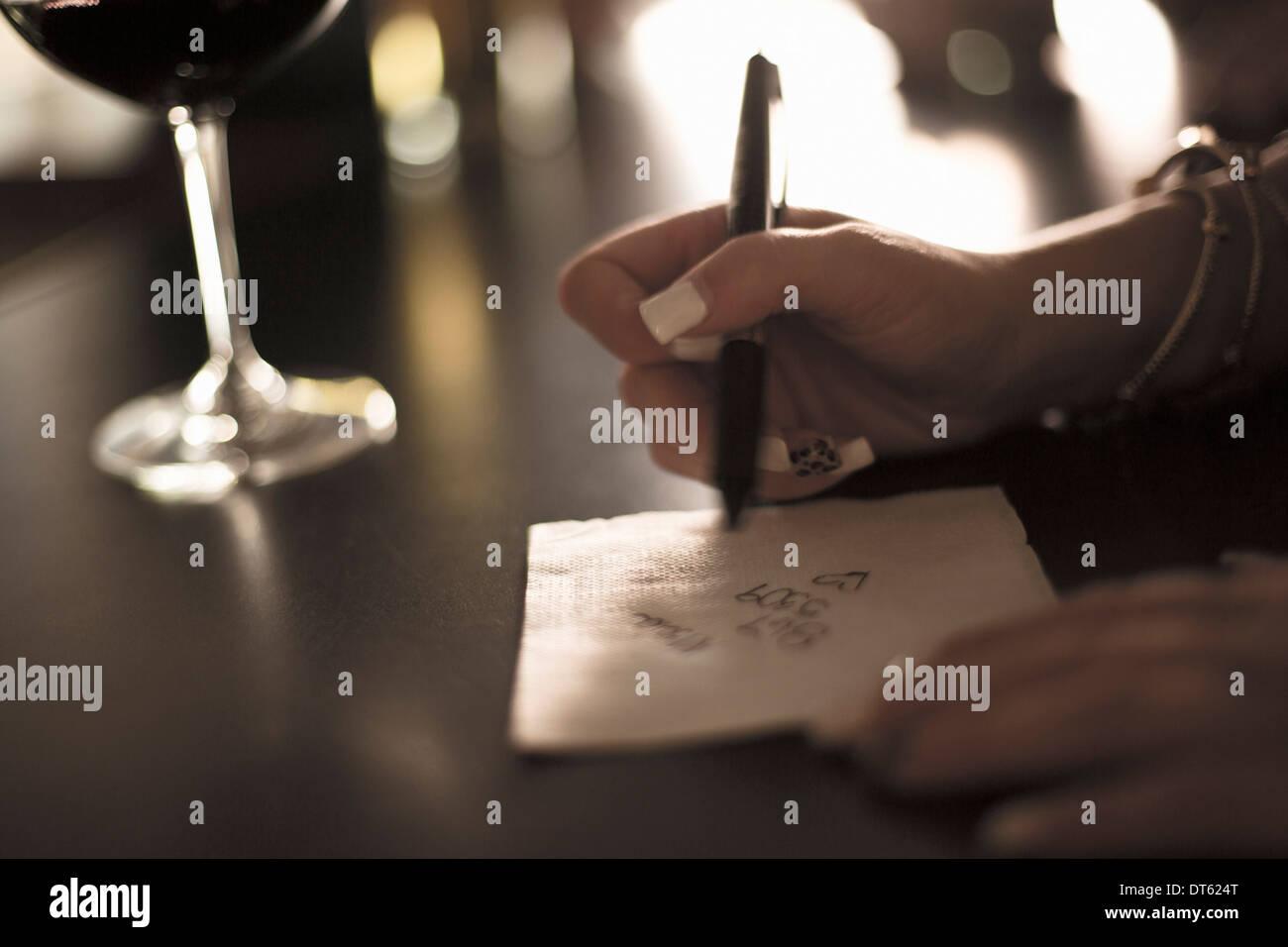 Cerca de joven mujer escribe su número de teléfono en una servilleta de papel de un bar Imagen De Stock