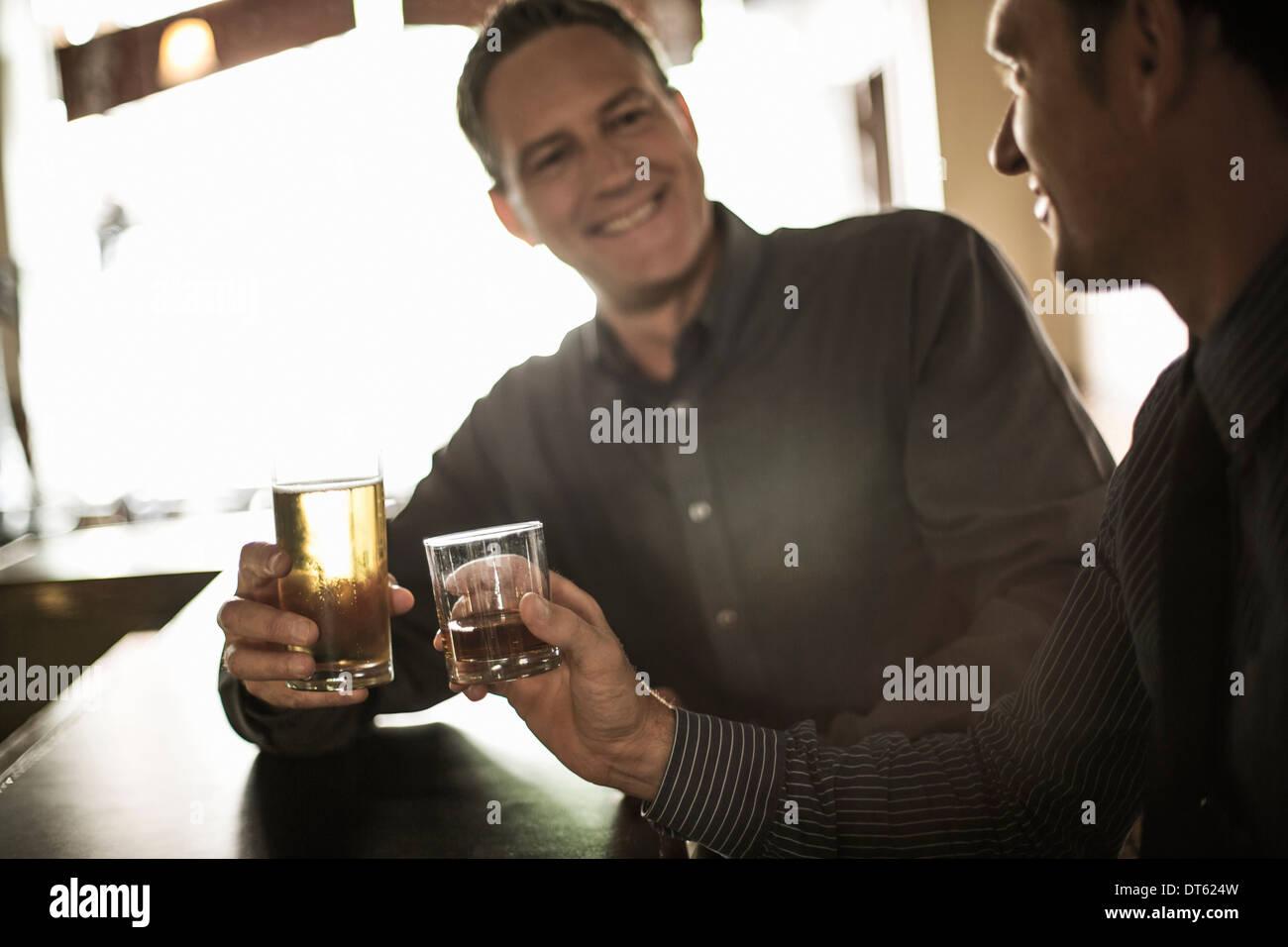 Dos hombres de negocios tostado de bebidas en el bar Imagen De Stock
