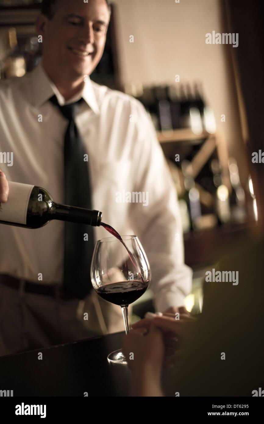 Barman, verter el vino tinto en bares Imagen De Stock
