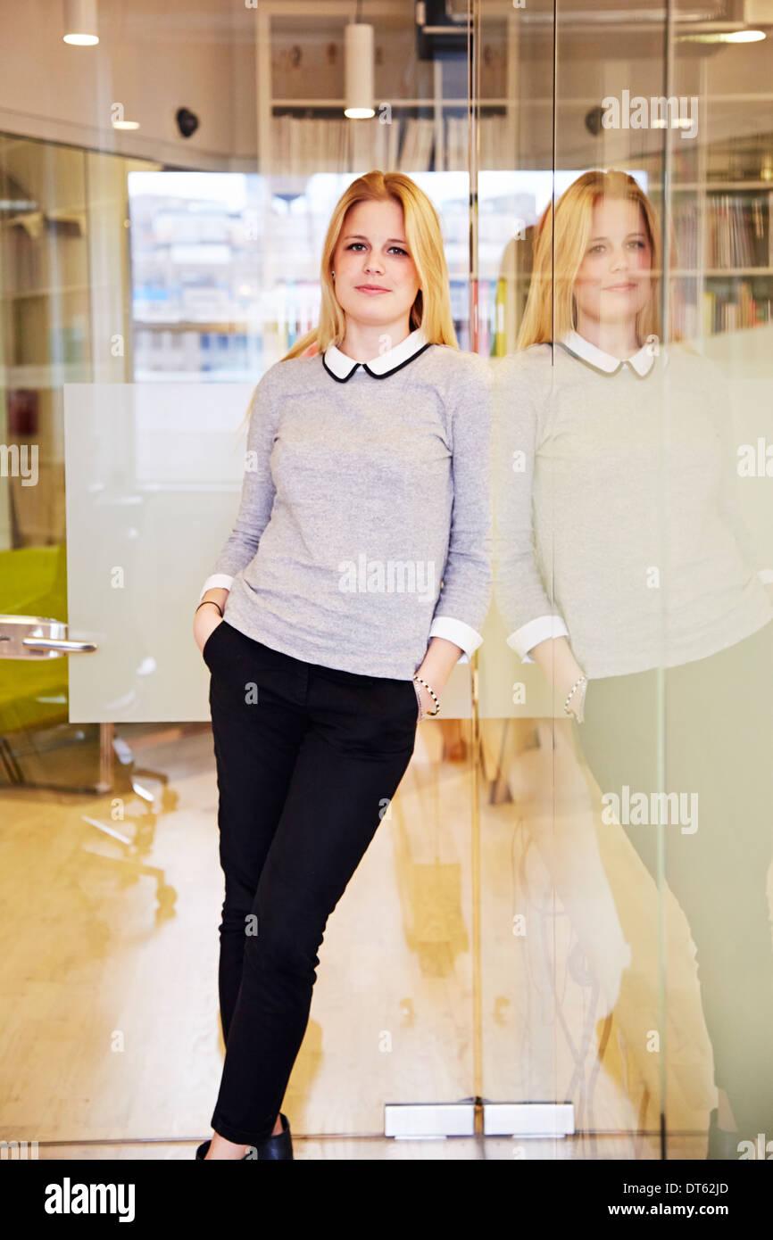 Trabajador de oficina femenina apoyada contra el vidrio Imagen De Stock