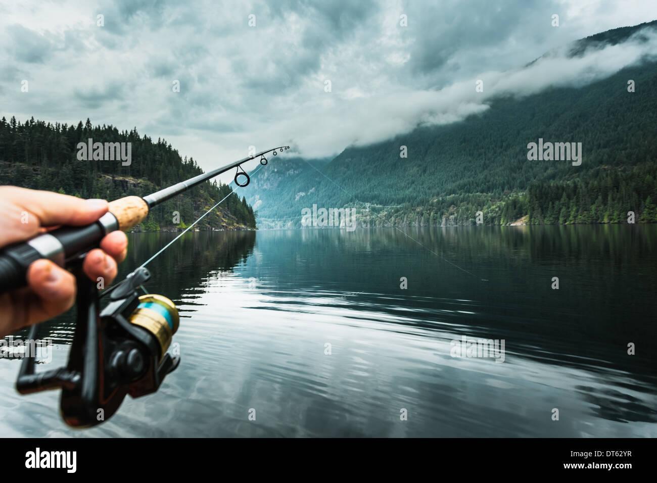 Hombre sujetando la barra de pesca cerca, Buntzen Lake, British Columbia, Canadá Imagen De Stock