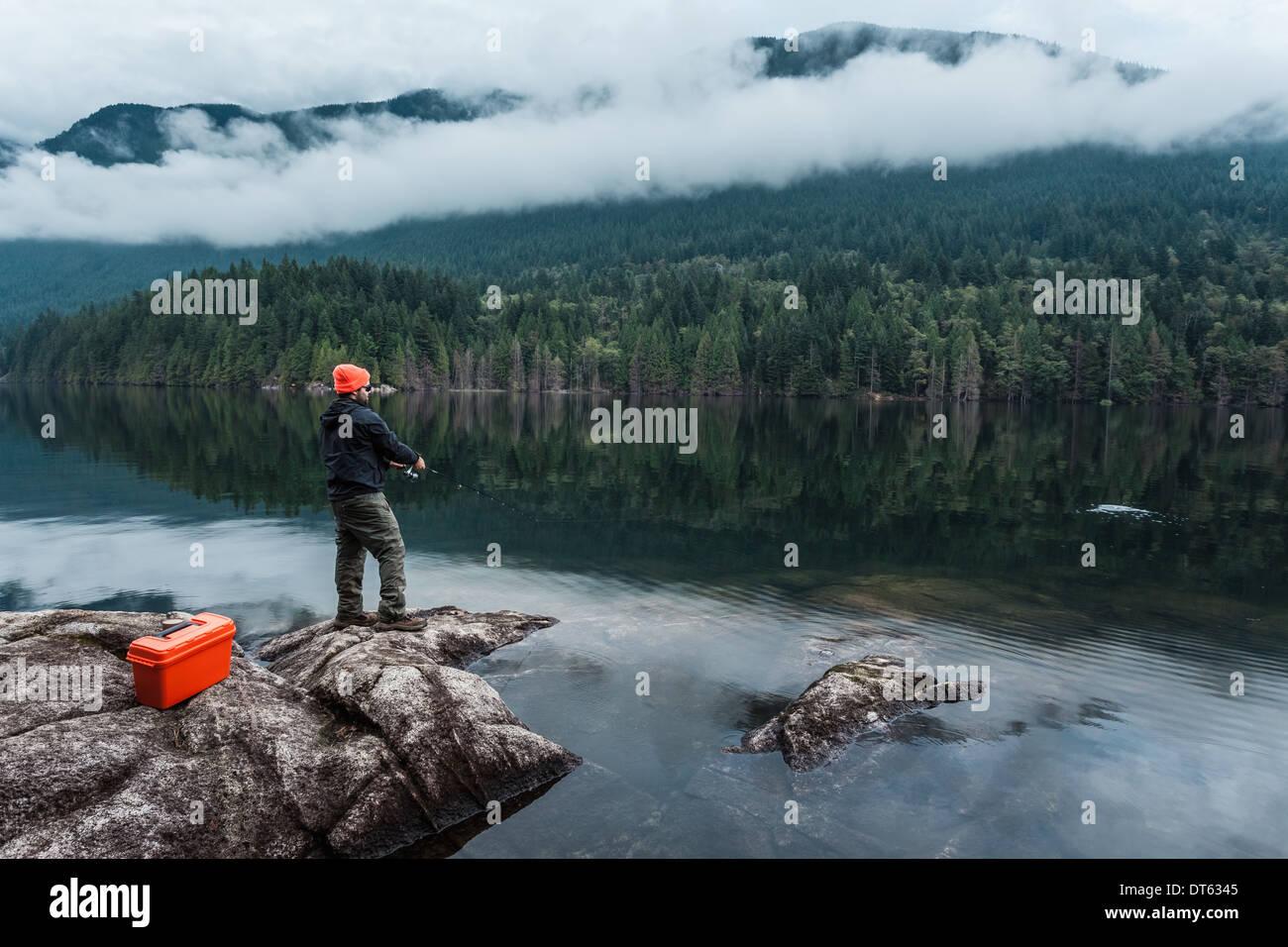 El hombre la pesca desde rocas, Buntzen Lake, British Columbia, Canadá Imagen De Stock