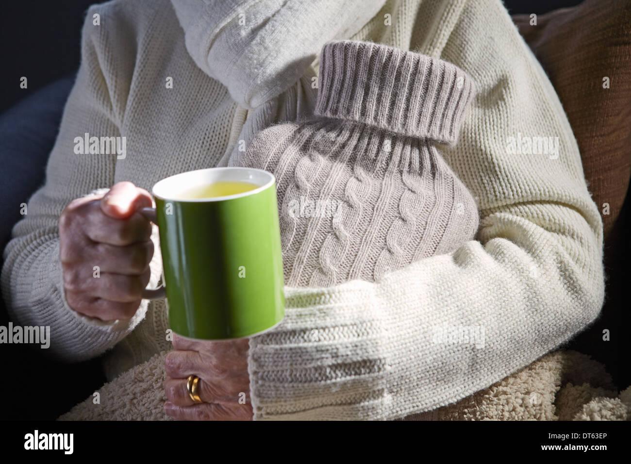 Mujer sosteniendo senior de taza y una botella de agua caliente Imagen De Stock