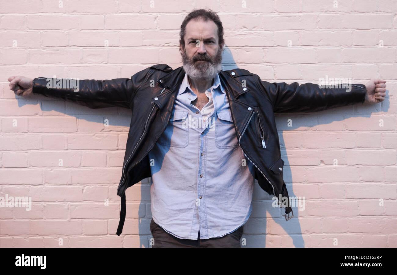 Hombre maduro por pared de ladrillo con los brazos Imagen De Stock