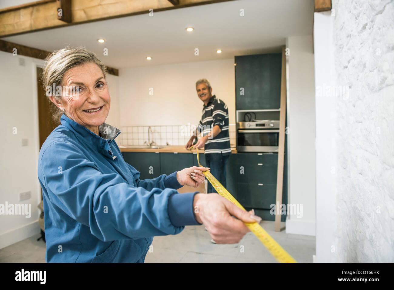 Las parejas ancianas haciendo bricolaje, utilizando cinta métrica Foto de stock