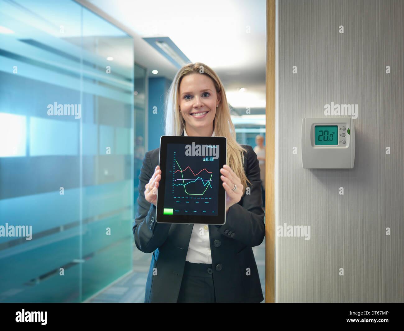 Retrato de trabajador de oficina celebración tablet digital junto a Office ajusta el termostato para ahorrar energía Imagen De Stock
