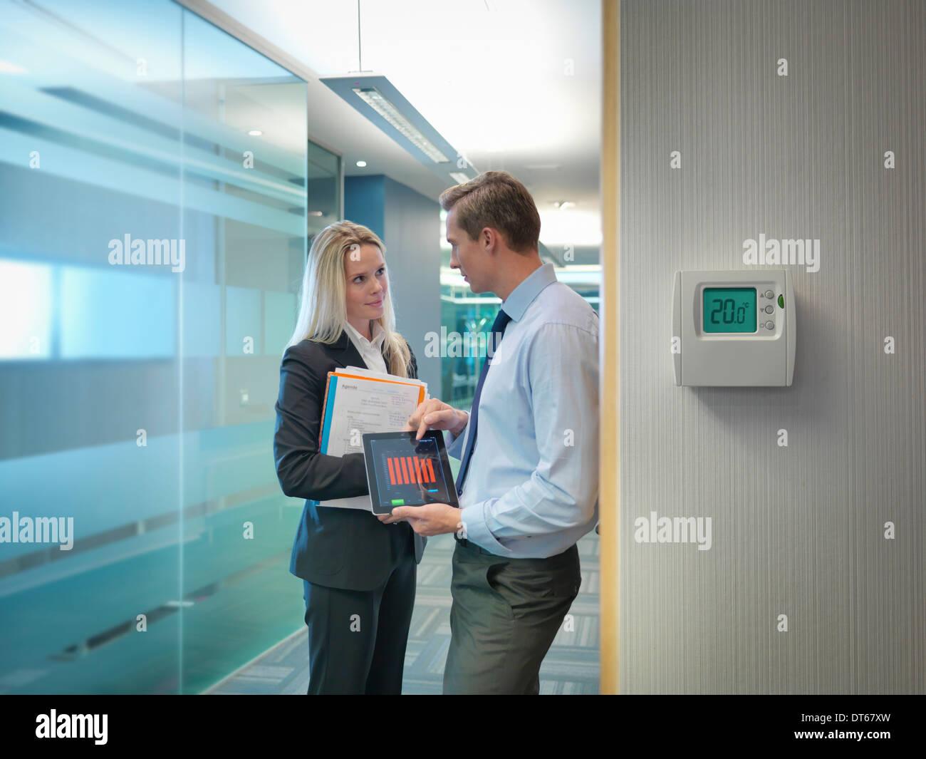 Los trabajadores de oficina y archivos digitales holding tablet discutiendo el uso de energía de oficina Imagen De Stock