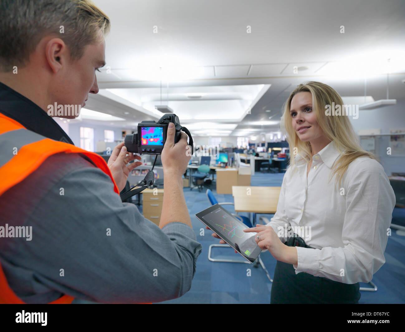 Los trabajadores de la oficina de tomar imágenes en el infrarrojo térmico en la oficina para verificar la eficiencia térmica Imagen De Stock