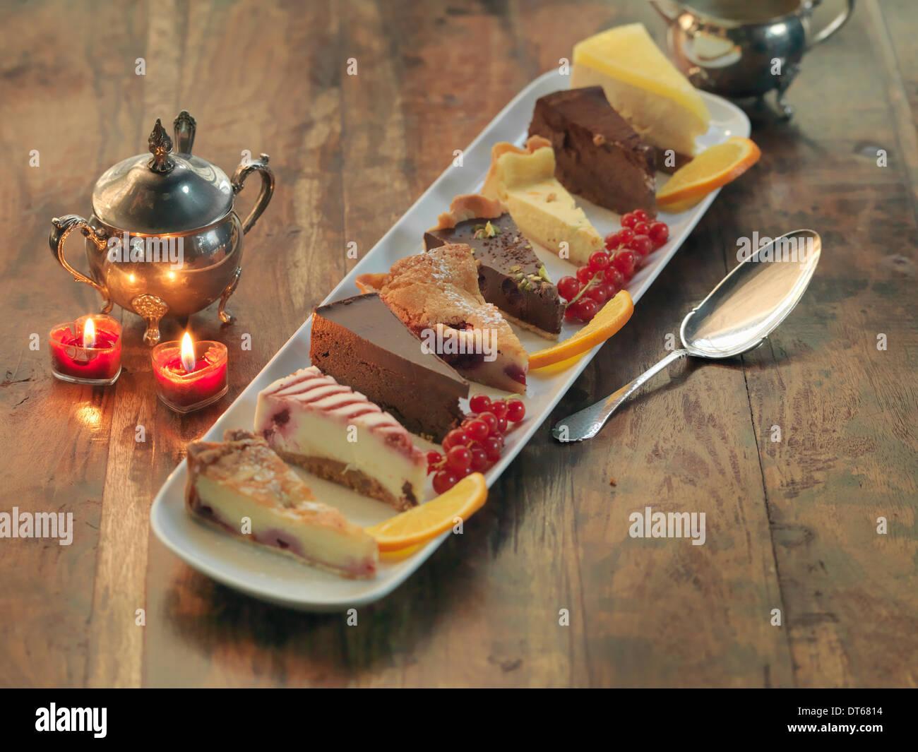 Plato mixto de pasteles y tartas entre decoraciones festivas Imagen De Stock