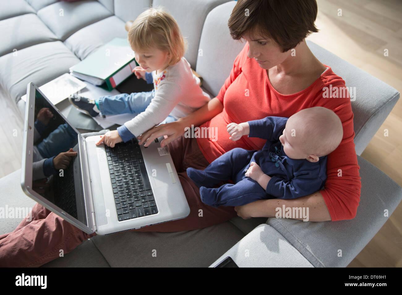 Madre, varón y hembra toddler utilización portátil en el sofá Imagen De Stock
