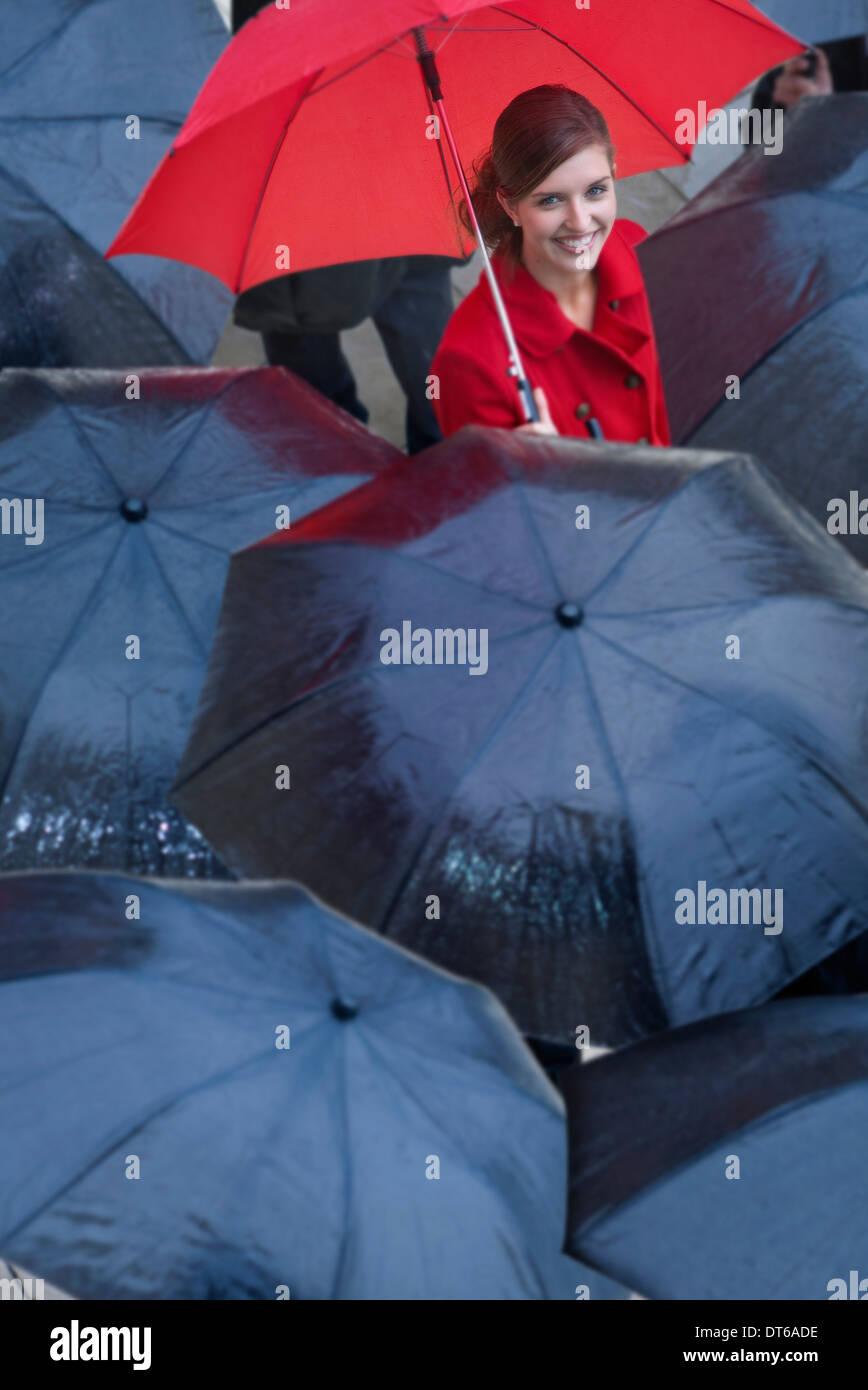 Mujer joven con sombrilla roja entre los Paraguas negro Foto de stock