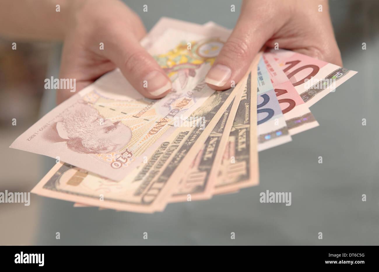 Manos sosteniendo femenino estadounidense, británica y la moneda europea. Imagen De Stock