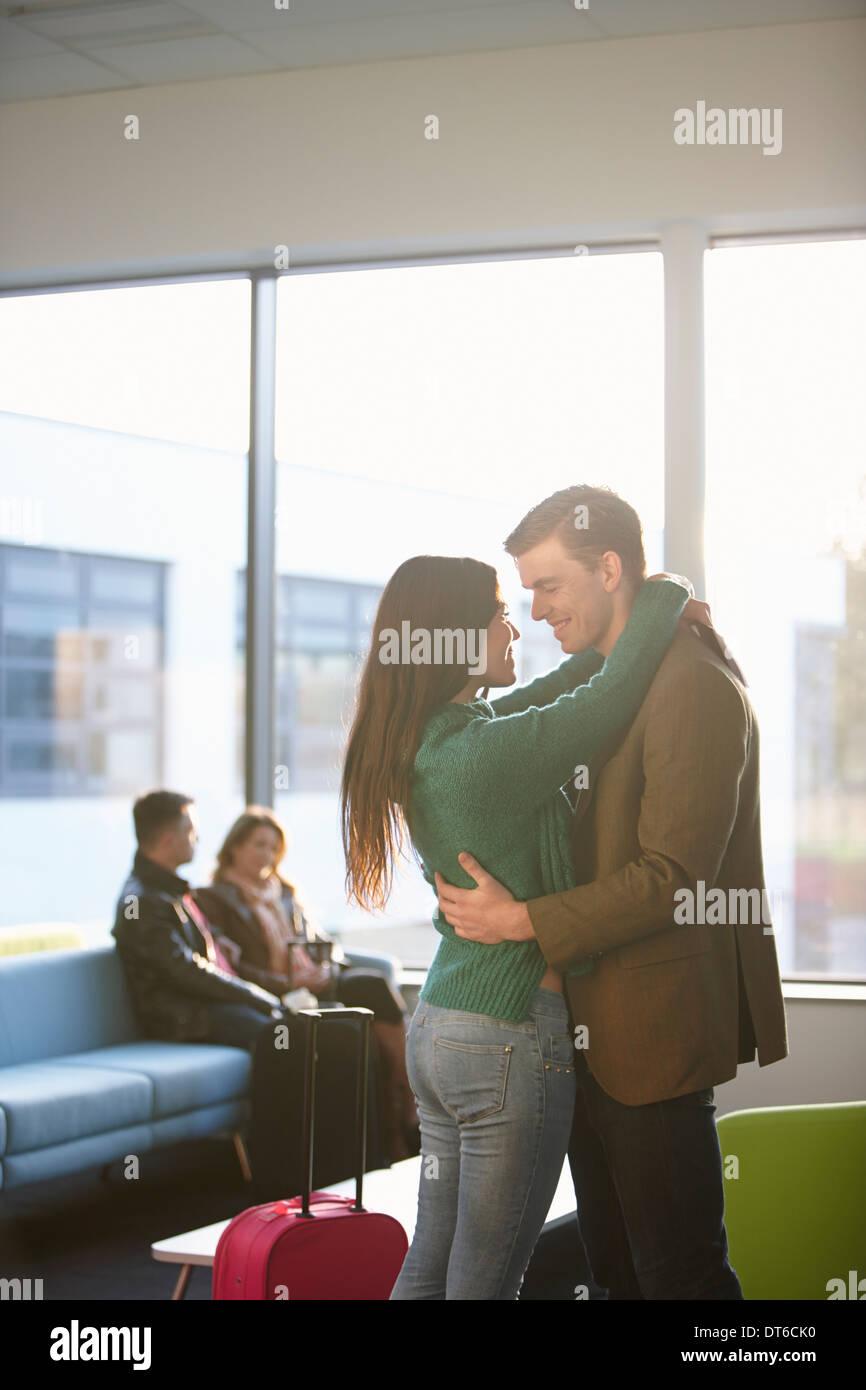 Pareja joven abrazando en aeropuerto Imagen De Stock