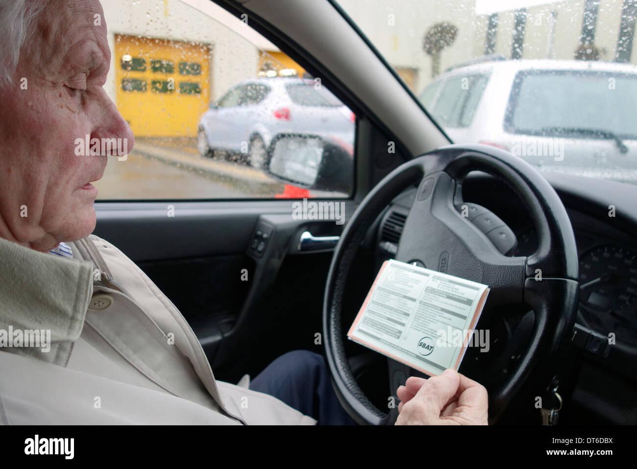 Anciano mirando SBAT tarjeta en coche mientras la cola delante del MOT centro de pruebas para un vehículo de motor de inspección anual Imagen De Stock