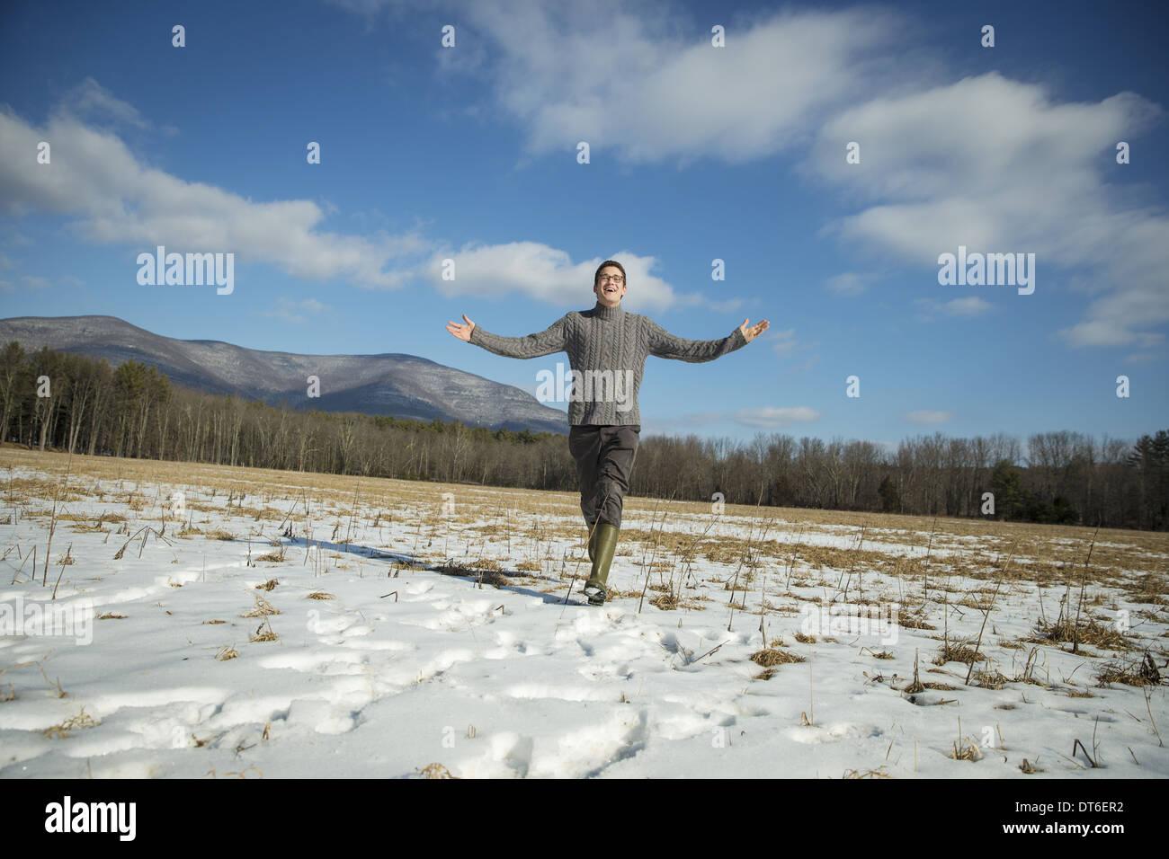 Un hombre en un cable puente tejida y muck botas de pie con los brazos estirados, cubierto de nieve en un paisaje rural. Imagen De Stock
