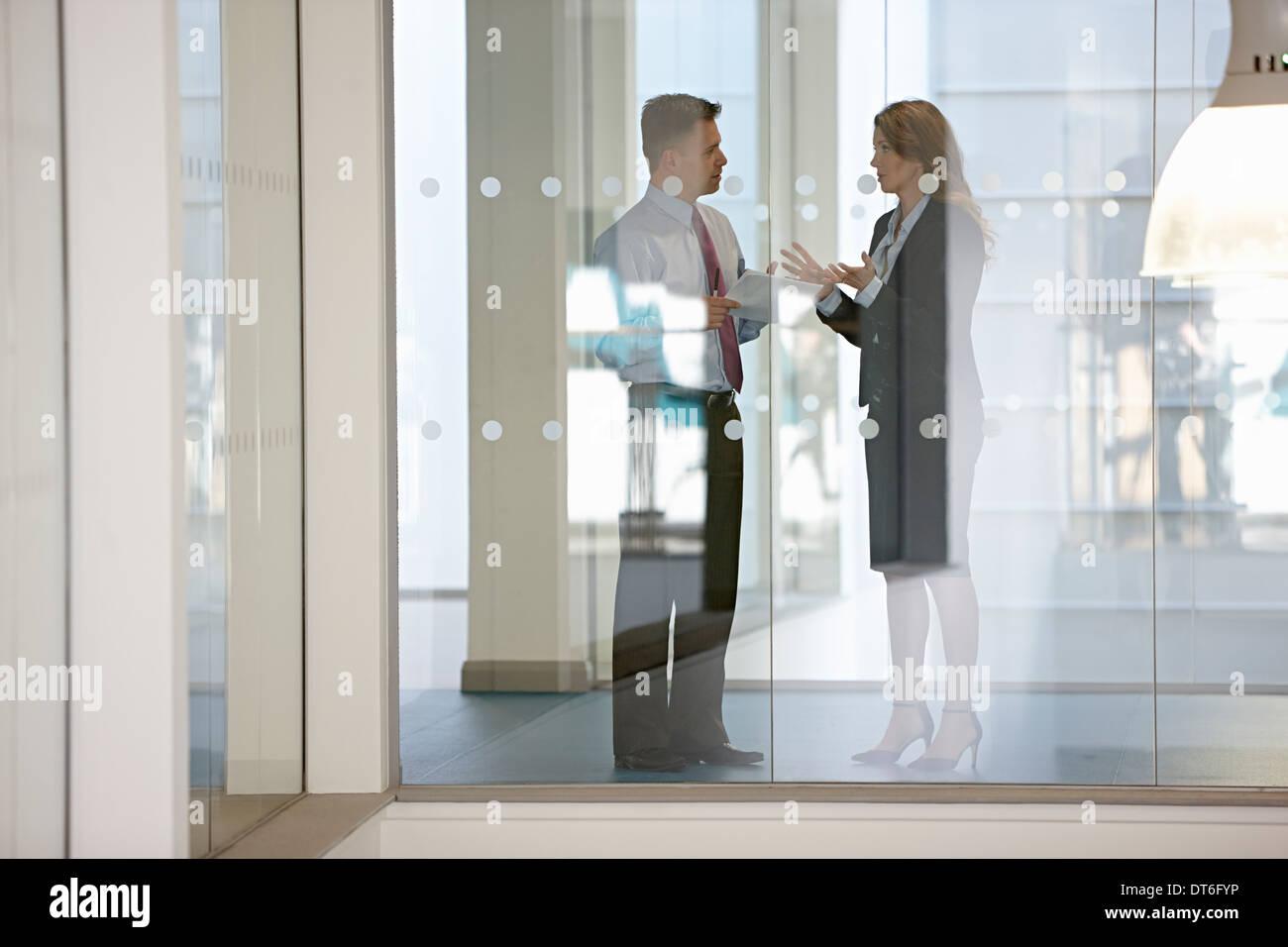 Los compañeros de negocio en la discusión a través del cristal Imagen De Stock