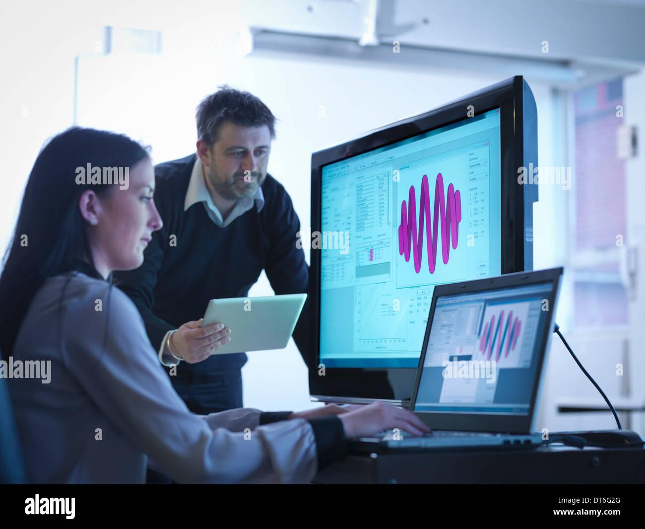 Los trabajadores que utilizan software para calibrar los muelles en Office Imagen De Stock