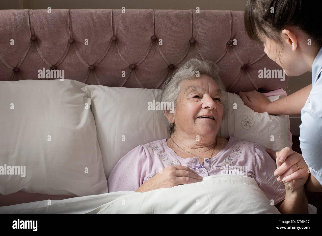 Asistente de cuidado personal charlando con mujer mayor en la cama Imagen De Stock