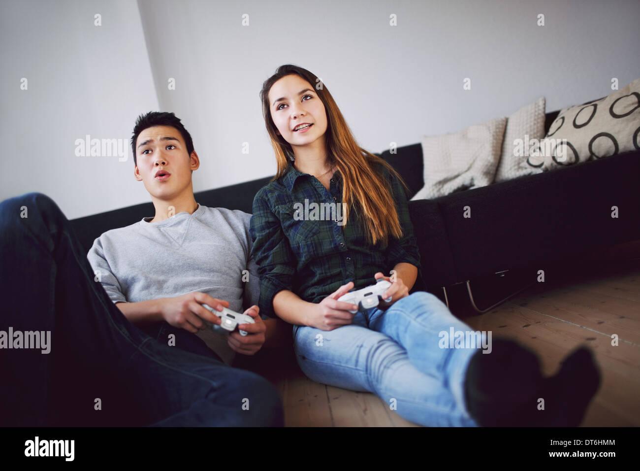 Pareja joven jugando juegos de video juntos mientras está sentado en su sala de estar. La pareja de adolescentes de raza mixta la celebración de juegos de vídeo. Imagen De Stock