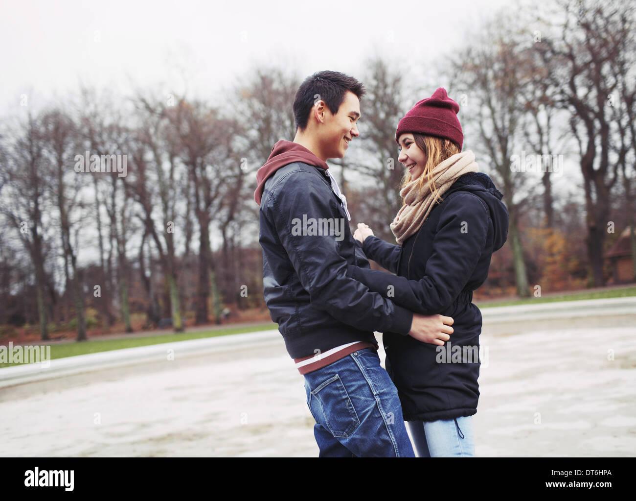 Apuesto joven y bella mujer de pie juntos miran sonrientes. Adolescentes de raza mixta par en amor Imagen De Stock