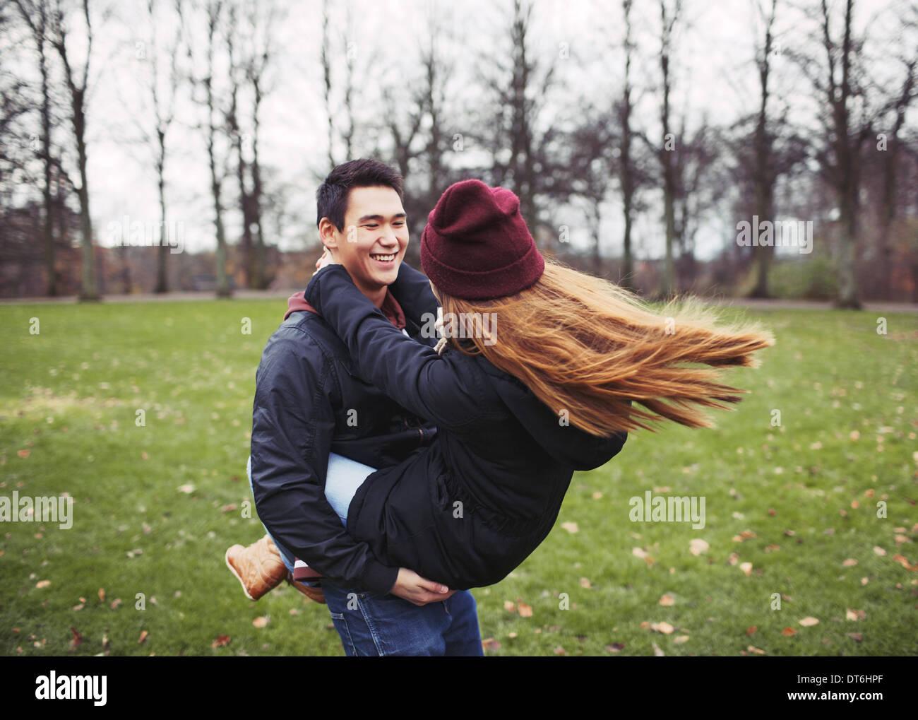 Apuesto joven llevando a su novia en el parque. Pareja joven asiática divirtiéndose al aire libre. Imagen De Stock