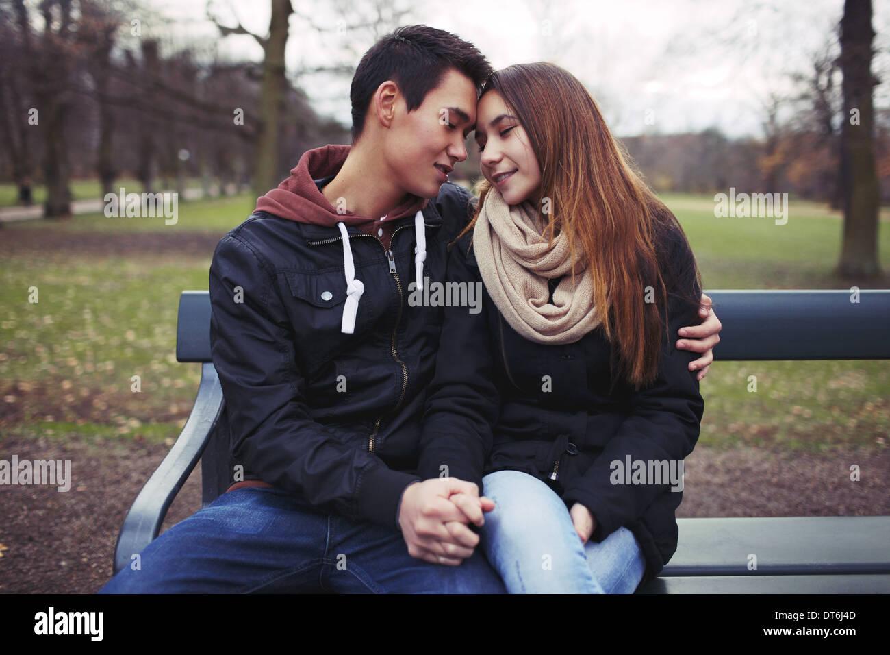 Pareja joven compartiendo un momento de licitación, mientras están sentados en un banco del parque. Adolescentes pareja asiática al aire libre en el parque. Imagen De Stock